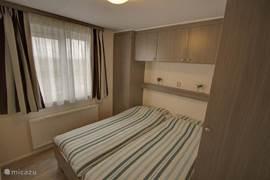 De grote slaapkamer met king-size bed. Aan weerskanten grote kasten met legplanken en hangers.