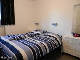 De ouderslaapkamer met 2 eenpersoonsbedden, bedlampjes en ladenkasten.