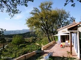 Kom je via de trap omhoog, dan zie je het huis zo liggen. Het terras kijkt uit over een vallei met wijngaarden en de baai van La Ciotat. Het is hier 's morgens heerlijk ontbijten in de schaduw en in de avond dé plek om te mijmeren met een glas wijn in de hand. Hier heeft u het mooiste uitzicht.