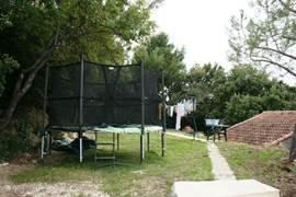 Vanaf het zwembadterras loopt u via het trapje achter het huis om naar de trampoline en de waslijn.  (gras is op de foto net ingezaaid)