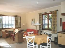 De woonkamer is licht en vriendelijk. Twee openslaande deuren naar het terras en opzij twee grote ramen.