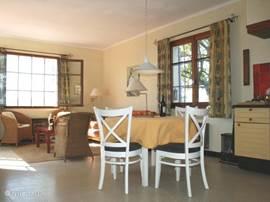 De ronde tafel heeft twee extra bladen, zodat je makkelijk met acht mensen aan tafel kunt. Er zijn acht eetkamerstoelen en nog een aantal losse krukken.
