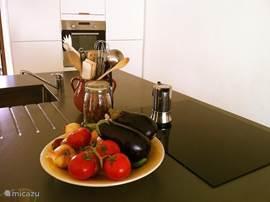 De moderne keuken is voorzien van dubbele koelkasten, afwasmachine en alles wat je nodig hebt om lekker te koken
