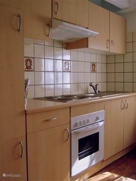 Aparte keuken met oven, magnetron, koffiezetapparaat, koelkast met vriesvak.