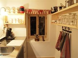 Kitchen with Senseo coffee machine, dishwasher, oven, hob, microwave, kettle, spice rack.