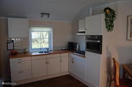 De Keuken met combimagnetron en koelvries combi. Vierpits gastoestel voorzien servies/ bestek en kookgerei