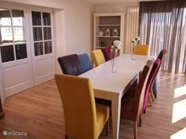 De ruime eetkamer met schuifdeuren naar de woonkamer en keuken.