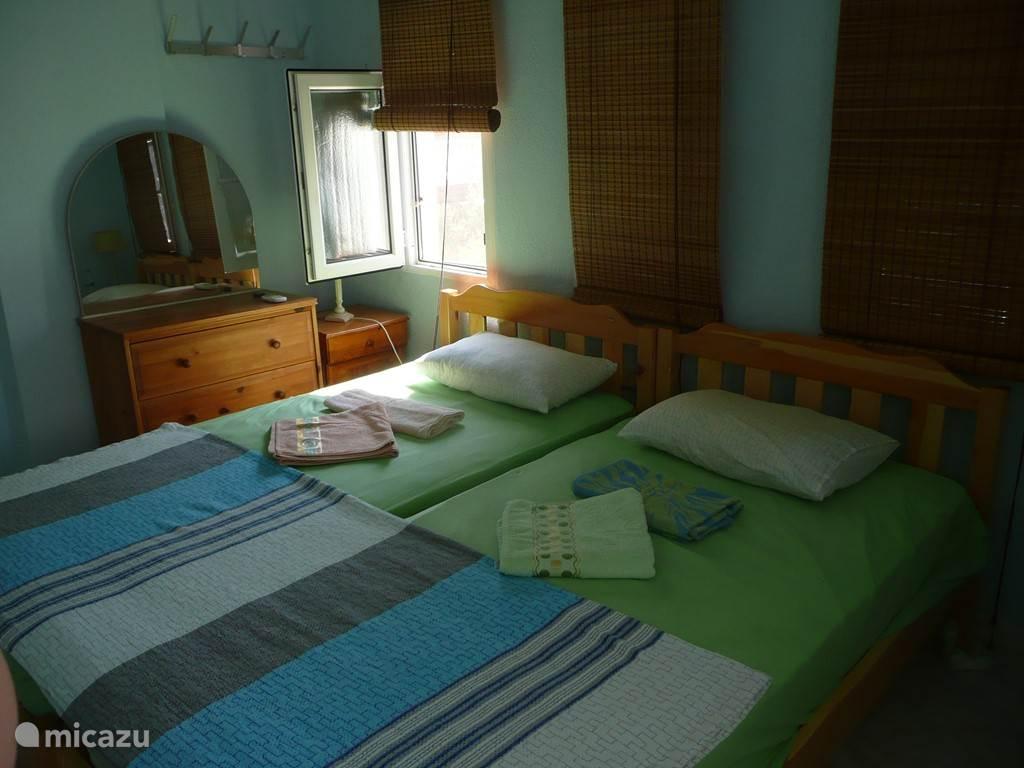 In de grote slaapkamer staan twee eenpersoonsbedden 100 x 200 cm, ladekast met spiegel en twee nachtkastjes