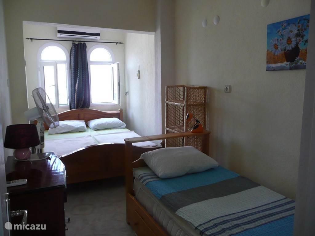De kleinere slaapkamer. Er staan één 2-persoonsbed en één 1-persoonsbed, rietenkast en een klein kastje met spiegel