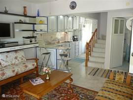 De woonkamer met de open keuken en de badkamer op de begane grond