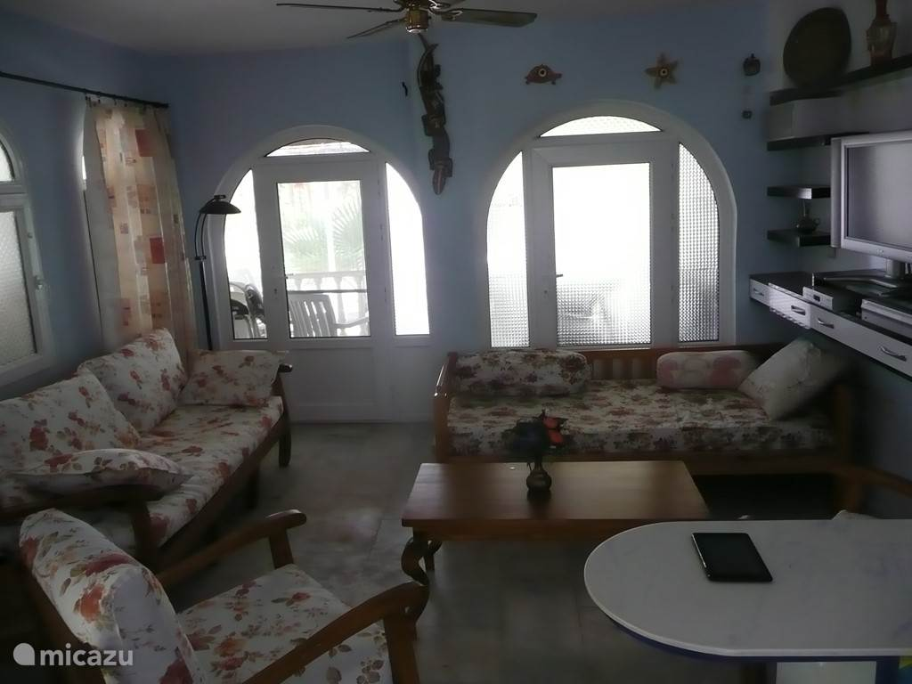 De zitkamer met de open keuken. Er zijn 2 sofa's, salontafel, 2 stoelen, TV, CD-speler e.a.