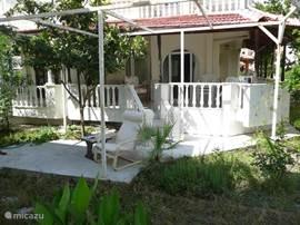 In de tuin vóór veranda is een betonnen plateautje voor een kinderzwembad of om erop te zonnen in het voor- of najaar