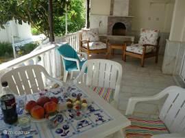 De L-vormige veranda met granieten BBQ en marmeren vloeren. In de hoek ervan is de beste afkoeling door de zeebreeze