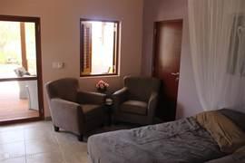 De woonkamer van de studio's met openslaande ramen en frenchdoors naar de porche en twee heerlijke fauteuils om lekker in te relaxen..
