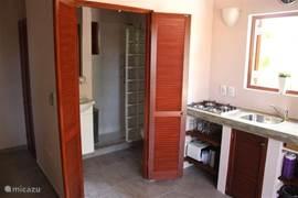 Inkijk in de badkamer. Naast wastafelmeubel een ruime douche met warm water en massagedouchekop. In de douche een rek voor de douchespullen. In de badkamer staat ook het toilet..