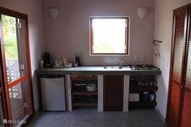 De keuken van de studio's met openslaande ramen, ook weer voorzien van shutters en horren, die volledig ingericht is met o.a. senseo koffiezetapparaat, 4 pits gasstel, waterkoker, oventje, koelkast, borden, bestek, pannen, glazen etc.