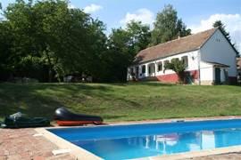 Een goed beeld van het zwembad van 9x4 meter met het huis en walnotenboom plus terras op de achtergrond.