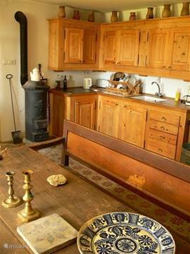 De nieuw gebouwde keuken in 2008 met keramische plaat en een antieke houtkachel die veel warmte afgeeft.