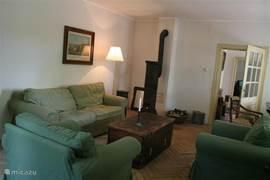 De woonkamer met antieke houtkachel, fauteuils en slaapbank.