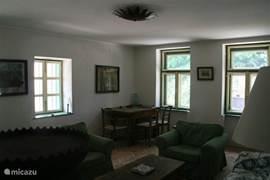 De woonkamer gezien vanaf de houtkachel op de vorige foto. 's Nachts kunnen de luiken dicht en de ramen open zodat eekhoorns en andere dorpsbewoners niet naar binnen kunnen.