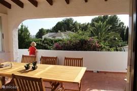 Ruim overdekt terras met luxe tuinset voor zes personen.