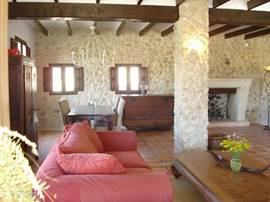De koloneale meubels staan ruim opgesteld in een kamer waar oude houten plafond balken,authentieke stenen muren en een grote openhaard het decor vormen