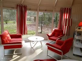 De kleurige en lichte woonkamer van onze ronde vrijstaande 4 persoonsbungalow Middagten.
