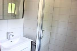 Badkamer voorzien van ruime douchecel met massagedouche. Verder beschikt de badkamer over een wastafel met opbergruimte en spiegelkastje.
