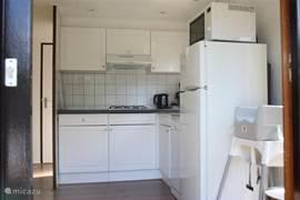 Keuken voorzien van alle gemakken zoals vaatwasser, koel/vriescombinatie, combimagnetron en vierpits gasfornuis (koken op gas).