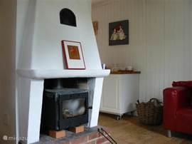 gezellige woonkamer met roden leren klippanbank, twee zwart leren poäng stoelen en een knusse houtkachtel.