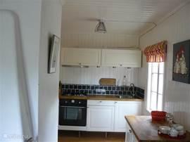 Kleine maar complete keuken met gasfornuis en oven.