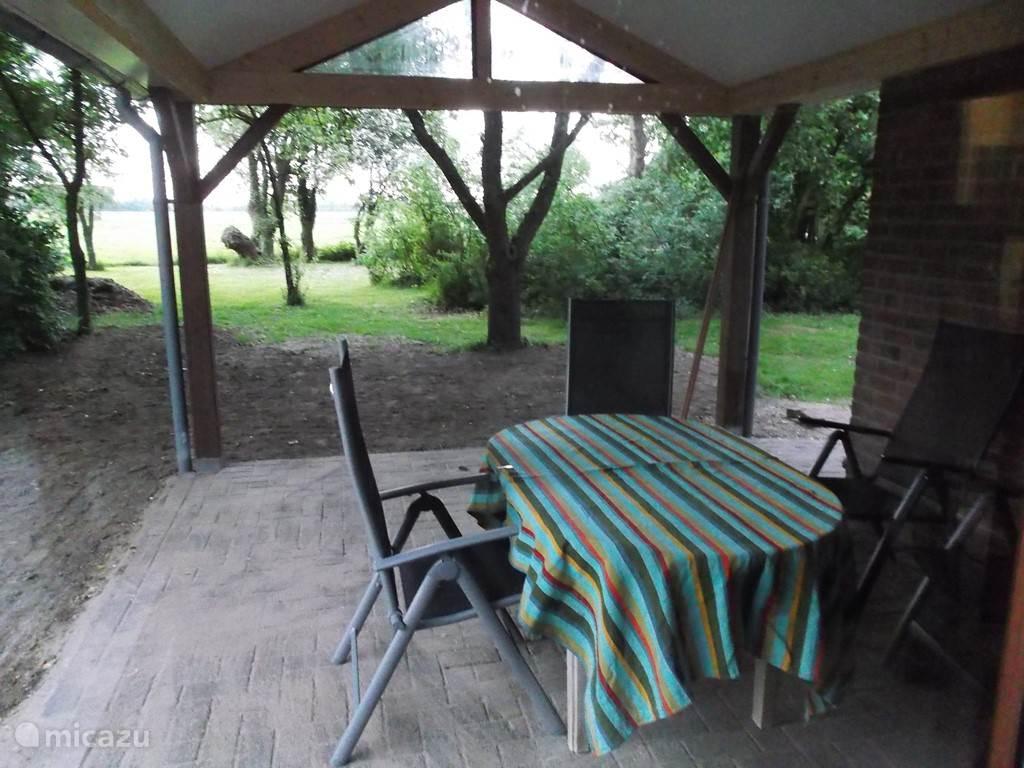 Op het nieuwe overdekte terras kunt u gezellig buiten eten met uitzicht over de tuin met de goudreinet fruitboom en het weiland met de koeien en de knotwilgen