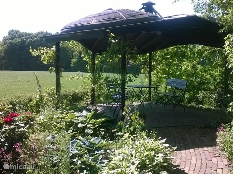 Achter in de tuin is er een ruim overdekt terras met uitzicht over de landerijen. Er is verlichting aanwezig, zodat u hier ook de avonden kunt doorbrengen. Het dak van de overkapping zorgt voor verwarming van het zwembad.