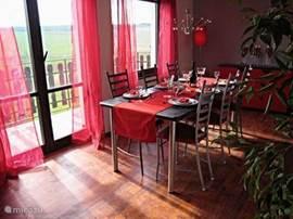 De eetkamer bevindt zich, net als de keuken, op de eerste verdieping. Hier kunt u bij de gezellige vlammen van de sfeerhaard en het sprookjesachtige licht van de  kroonluchter lekker lang tafelen.  Vanuit deze kamer hebt u een prachtig wijds uitzicht over de heuvels. Door het hele huis en tuinis e