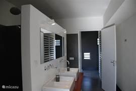 Beide badkamers hebben een regendouche, dubbele wastafel en toilet.