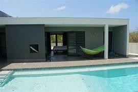 Vanuit de hoofdslaapkamer duik je 's-morgens zo het zwembad in (of de hangmat).