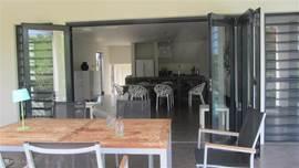 Woonkamer sluit aan op de grote veranda waardoor binnen en buiten leven naadloos in elkaar overlopen.