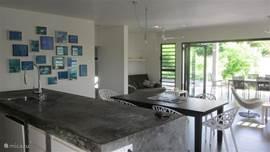 Ruime living, met 6 persoons eettafel en design stoelen zowel binnen als buiten op veranda.