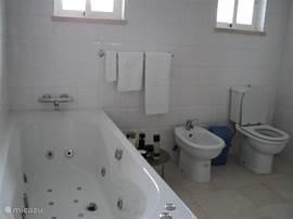 Grote badkamer met bubbelbad om heerlijk te badderen.