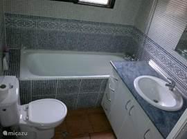 Badkamer  met aparte douchecabine en extra douchegedeelte in het ligbad (onderdeel van het huis)