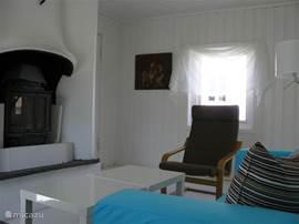 Deel van de gezellige witgeschilderde huiskamer met inzethaard. Met een turqoise tweezitsbank (klippan) en 2 poang fauteuils.