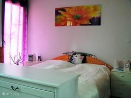 U bed hoeft u niet meer op te maken, dat is al voor u gedaan! Deze ruime, en zomers koele hoofdslaapkamer bevat een 2-persoons bed met 2 aparte matrassen van 80 x 200.  Een ruime garderobekast met spiegeldeuren doet de kamer nog ruimer lijken. Gratis bedlinnen.