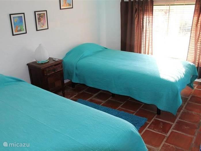 Slaapkamer met twee 1 persoonsbedden, bereikbaar via de trap vanuit de woonkeuken.