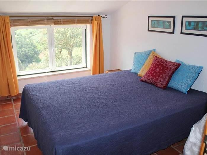 Slaapkamer met tweepersoonsbed, bereikbaar via de trap vanuit de woonkeuken.