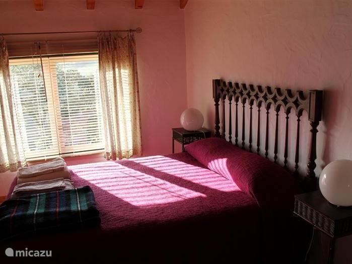 Slaapkamer met tweepersoonsbed en ruimte voor een extra bed, bereikbaar via de trap vanuit de huiskamer.