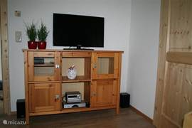 The cabinet with TV and radio / DVD player is in front of the bank.