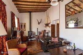 Koliniaal ingerichte zitkamer met zeer comfortabele fauteuils, houtkachel en Satelliet TV met o.a. Nederlandse zenders.