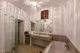 Grote badkamer met ligbad, aparte douche, dubbele wastafel en vloerverwarming.