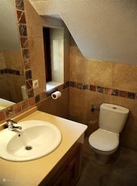 De badkamer en suite is voorzien van een wastafel, toilet,  inloopdouche en heater.