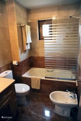 De tweede badkamer heeft een wastafel, toilet, bidet, ligbad en heater.